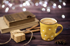Mug of coffee, cookies, star anise, cinnamon, old books. Blurred lights, wooden background. Winter time, Rustic background Stock Photos