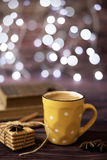 Mug of coffee, cookies, star anise, cinnamon, old books. Blurred lights, wooden background. Winter time, Rustic background Royalty Free Stock Image