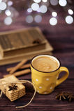 Mug of coffee, cookies, star anise, cinnamon, old books. Blurred lights, wooden background. Winter time, Rustic background Stock Photography