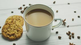 Mug with coffee and cookies. White cup with coffee and milk on white wooden table with cookies and coffee grains on top around stock video footage