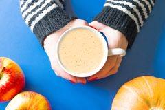Mug of coffee in the hands of a woman with leaves and pumpkin Royalty Free Stock Photography