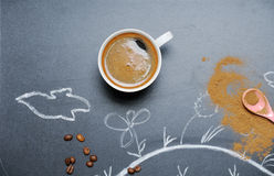 Mug of coffee with happy drawing and cinnamon on the blackboard Royalty Free Stock Images
