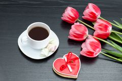 Mug of coffee and heartshaped gingerbread, five pink tulips. Black background. Mug of coffee and heartshaped gingerbread, five pink tulips. Black background royalty free stock photos