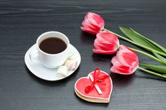 Mug of coffee and heartshaped gingerbread, three pink tulips. Bl. Ack background royalty free stock photo
