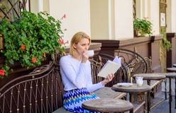 Mug coffee and interesting book best combination perfect weekend. Girl drink coffee while read bestseller book by. Popular author. Woman have drink cafe terrace stock image