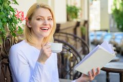 Mug coffee and interesting book best combination perfect weekend. Woman have drink cafe terrace outdoors. Find. Opportunity to read more. Girl drink coffee stock photography