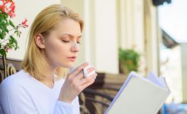 Mug coffee and interesting book best combination perfect weekend. Woman have drink cafe terrace outdoors. Girl drink. Coffee while read new bestseller book by royalty free stock images
