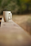 Mug of coffee on a ledge or wall. Viewed looking down the lenth of the tiles with shallow dof and copyspace in a conceptual image stock photo