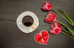 Mug of coffee, marshmallows and heartshaped gingerbread, three pink tulips. Black background.  stock photos