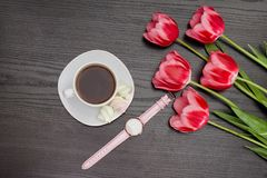 Mug of coffee, marshmallows, watch and three pink tulips. Black background Royalty Free Stock Photography