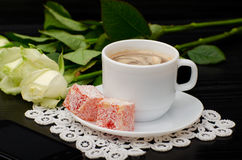 Mug of coffee with milk close-up, oriental sweets. smartphone, white roses on a black background.  Royalty Free Stock Photos