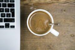 Mug of coffee near laptop Royalty Free Stock Image