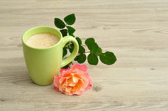A mug of coffee with an orange rose. On a wooden background stock photo