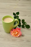 A mug of coffee with an orange rose. On a wooden background stock image