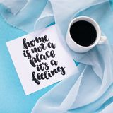 Mug of coffee on pale blue pastel chiffon cloth on a blue background. Card with handwritten inspirational quote Home is not a plac. E it`s a feeling royalty free stock image