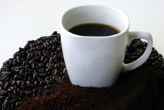 A Mug of Coffee Surrounded by Coffee Beans. This is a mug of coffee surrounded by coffee beans and grounded coffee.  Would be ideal for a Coffee Break sign Royalty Free Stock Photo