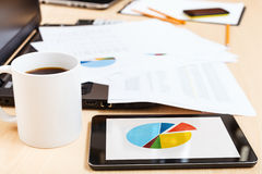 Mug of coffee and tablet pc with chart on desk Royalty Free Stock Image
