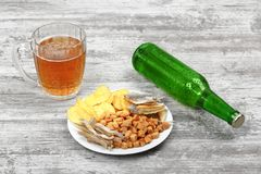 Mug of cold beer, bottle and snacks on the light wooden background. Chips, croutons, salted fish and peanuts. Top view. Stock Image