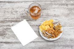 Mug of cold beer, snacks and blank sheet of paper on the light wooden background. Chips, croutons, salted fish and peanuts. Stock Image