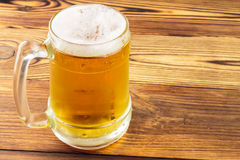 Mug of cold beer on wooden table Stock Images
