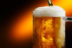 Mug of cold craft light beer on dark background.  royalty free stock photography