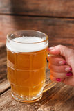 Mug of cold light beer on wood table, close up. Unrecognizable person holding mug with light beer in bar on wooden rustic table background. Close up view Stock Photography