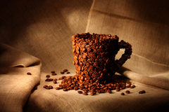 Mug covered with coffee beans Stock Photography