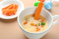 Mug with creamy soup for baby. On table stock image