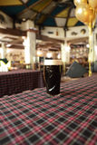 Mug with dark beer on a table Royalty Free Stock Image