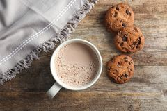 Mug with delicious hot cocoa drink and cookies. On wooden table, top view Royalty Free Stock Photo