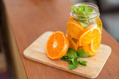 Mug delicious refreshing drink of orange fruit , infused water. Mug delicious refreshing drink of orange fruit with mint , infused water royalty free stock images