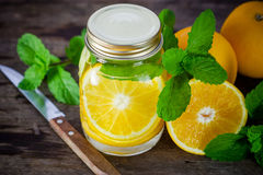 Mug delicious refreshing drink of orange fruit with mint Royalty Free Stock Image