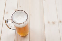 Mug of draft beer on wooden table Royalty Free Stock Images