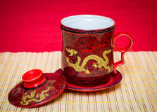 Mug with dragon. Beautiful red tea cup with a gold dragon and lid Royalty Free Stock Photos