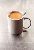 Mug of English tea. A still life mug of English breakfast tea which is placed on a brushed silver greasy spoon cafe in London England. The tea spoon is inside stock images
