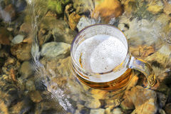 Mug of excellent beer sparkles in the sun in a mountain stream Stock Photography