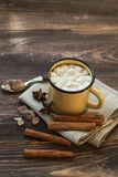 Mug filled with hot chocolate and marshmallows. At the old wooden table with cinnamon and brown sugar Stock Images