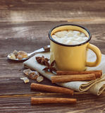 Mug filled with hot chocolate and marshmallows. At the old wooden table with cinnamon and brown sugar Royalty Free Stock Photography