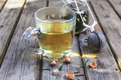 Mug of flavored green tea with rose buds and petals Stock Photos