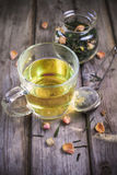Mug of flavored green tea with rose buds and petals Stock Image
