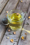 Mug of flavored green tea with rose buds and petals Royalty Free Stock Photos