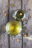Mug of flavored green tea with rose buds and petals Stock Images