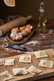 Mug flour, eggs, rolling pin, olive oil in a jar on a wooden background, making ravioli.  Stock Photo