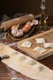 Mug flour, eggs, rolling pin, olive oil in a jar on a wooden background, making ravioli.  Royalty Free Stock Photography