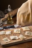 Mug flour, eggs, rolling pin, olive oil in a jar on a wooden background, making ravioli Stock Images