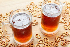 Mug of foamy beer alcohol with german pretzel. Traditional bavarian Oktoberfest snacks and drink. Royalty Free Stock Photography