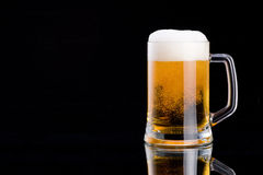 Mug fresh beer with cap of foam on a black Stock Images