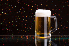 Mug fresh beer with cap of foam on colored light Royalty Free Stock Image