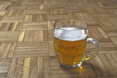 Mug of fresh beer with cap of foam. Stock Image