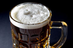 Mug of Fresh Beer with Foam Over Black Background Royalty Free Stock Images